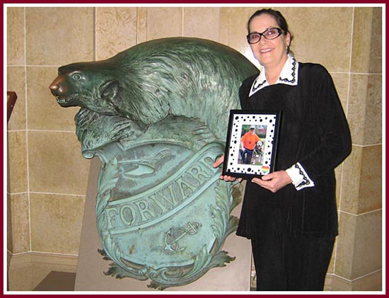"Eilene Ribbens of the Wisconsin Puppy Mill Project stands by a statue bearing the WI State motto ""FORWARD"" in the State Capitol in Madison as WI Act 90 was signed into law."